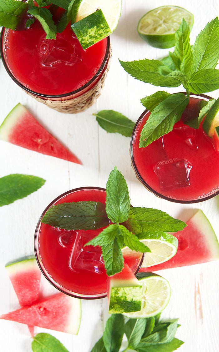 Overhead shot of watermelon agua frescas in three glasses on a white background.
