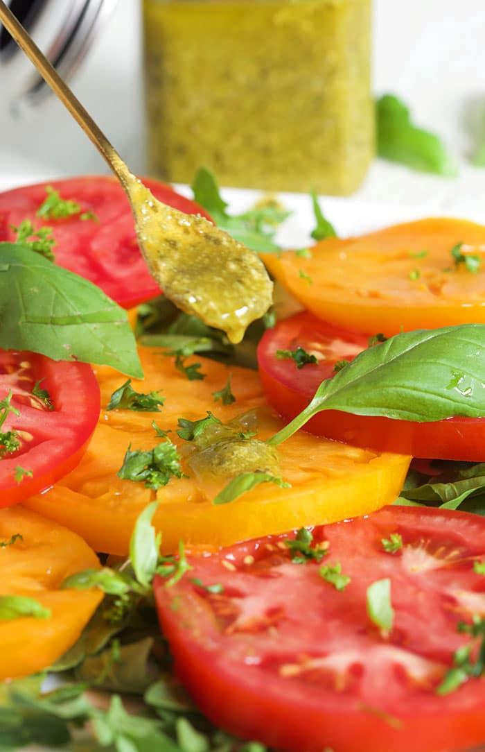 Basil Pesto Vinaigrette being spooned over a tomato salad.