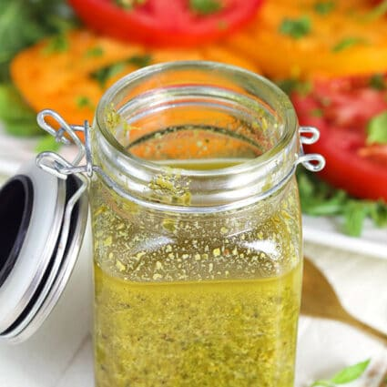 Basil Pesto Vinaigrette in a glass jar with a plate of tomatoes in the background.
