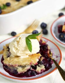 blueberry dump cake on a white plate with a scoop of ice cream and a gold fork.