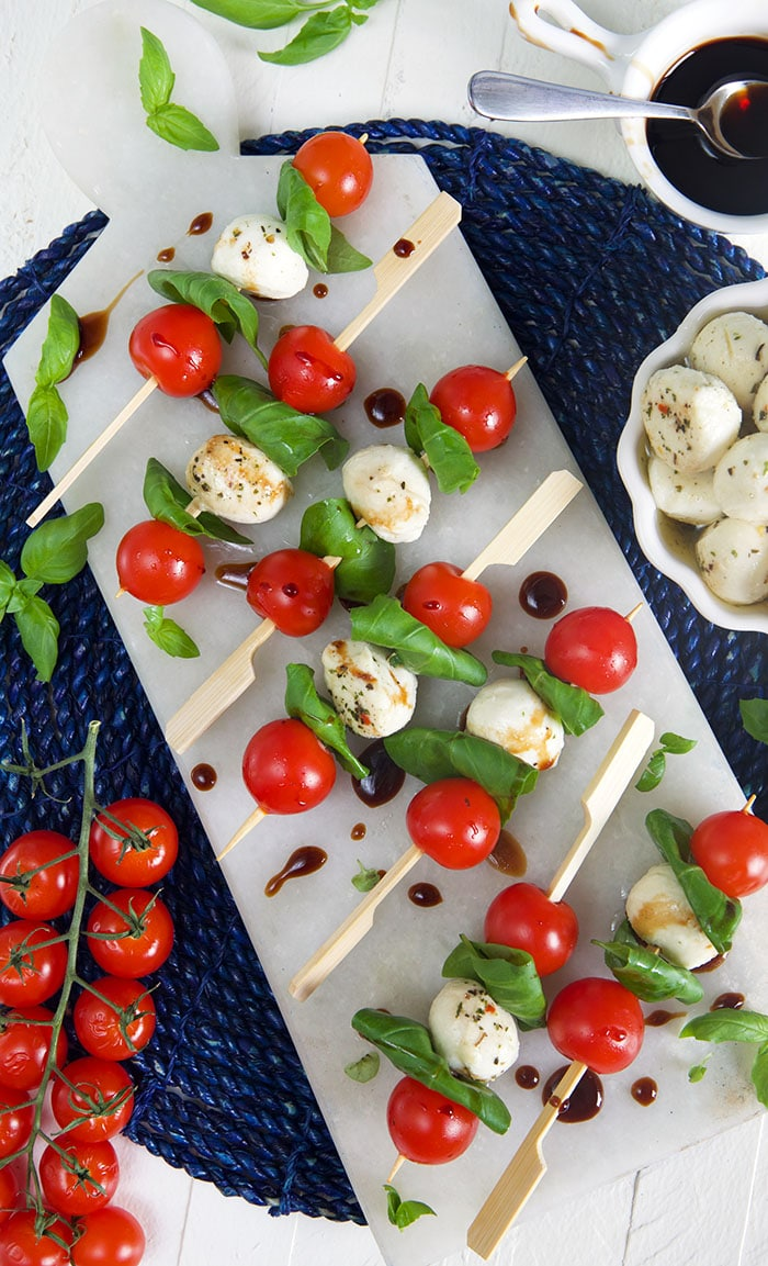 overhead shot of caprese skewers on a white marble board.