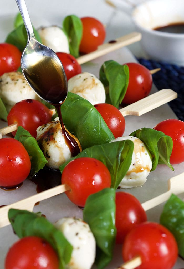 Caprese Skewers on a white board with balsamic glaze being drizzled on them.