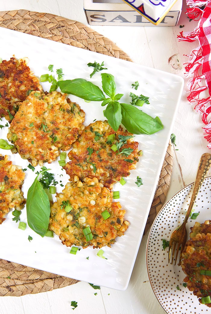 Overhead shot of corn fritters on white square platter with a red and white checked napkin.
