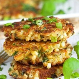 Three corn fritters are stacked on a white plate with a sprig of basil.