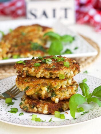 stacked corn fritters on a white plate with basil and a salt box in the background.