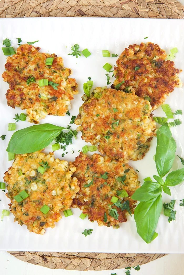Overhead shot of corn fritters on a white platter with basil.