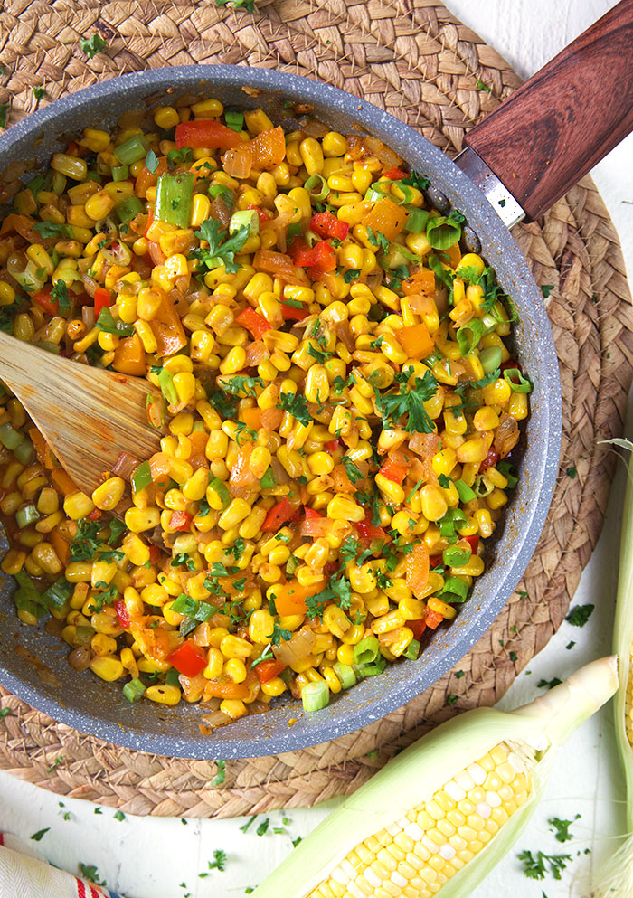 Corn Maque Choux in a skillet on a wicker placemat.