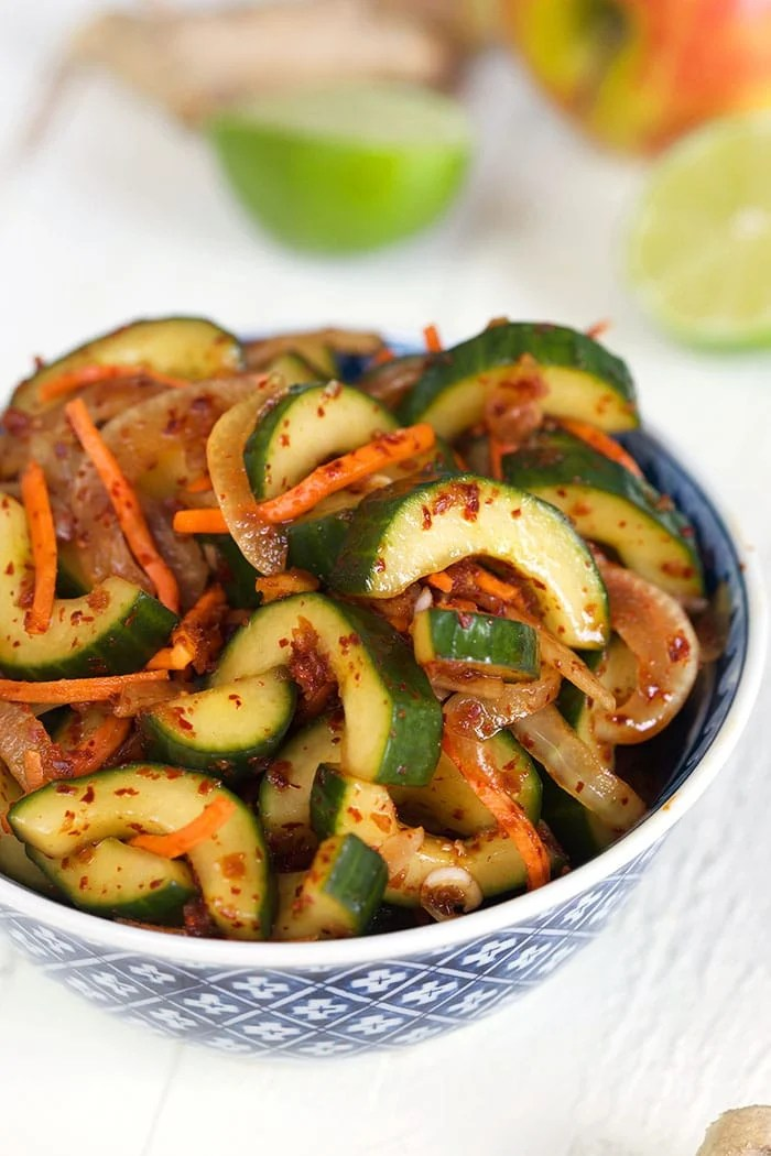 Cucumber Kimchi in a blue and white bowl on a white background.