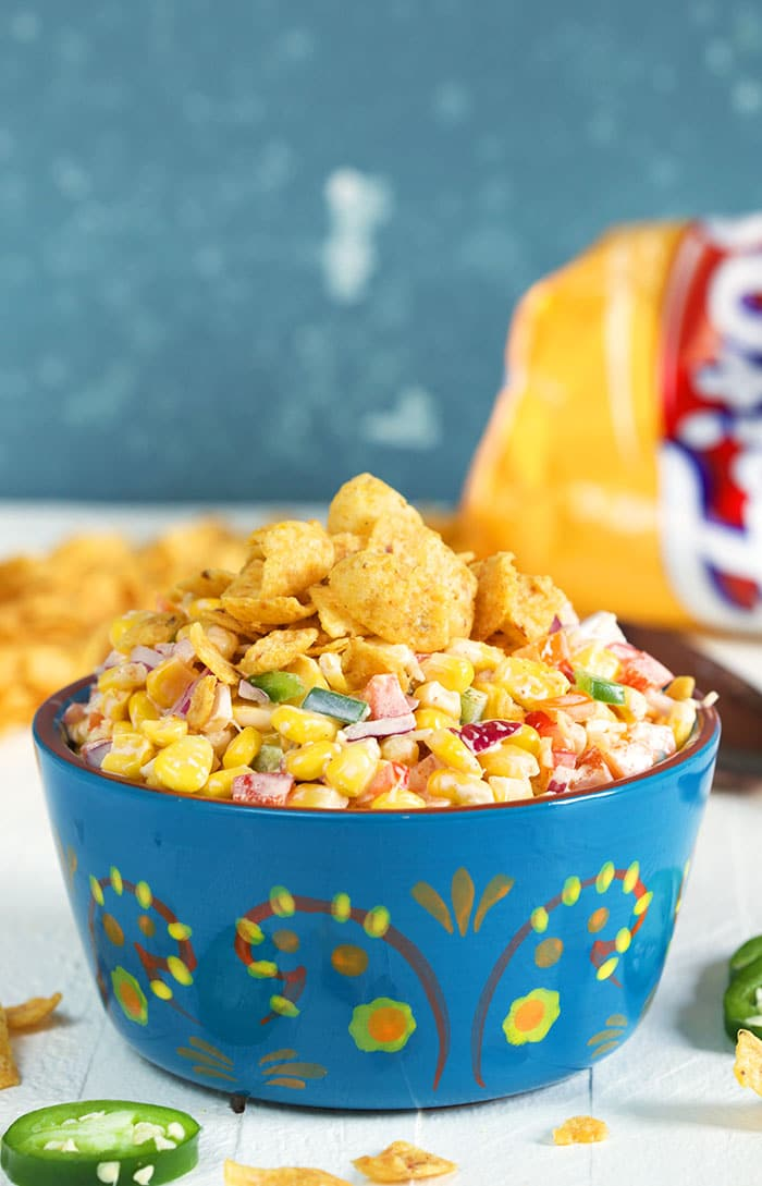 FritoCorn Salad in a blue terra cotta bowl with a bag of Fritos in the background.