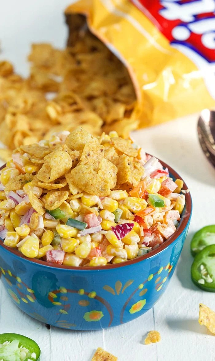 Frito Corn Salad in a blue bowl on a white background with Fritos in the background.