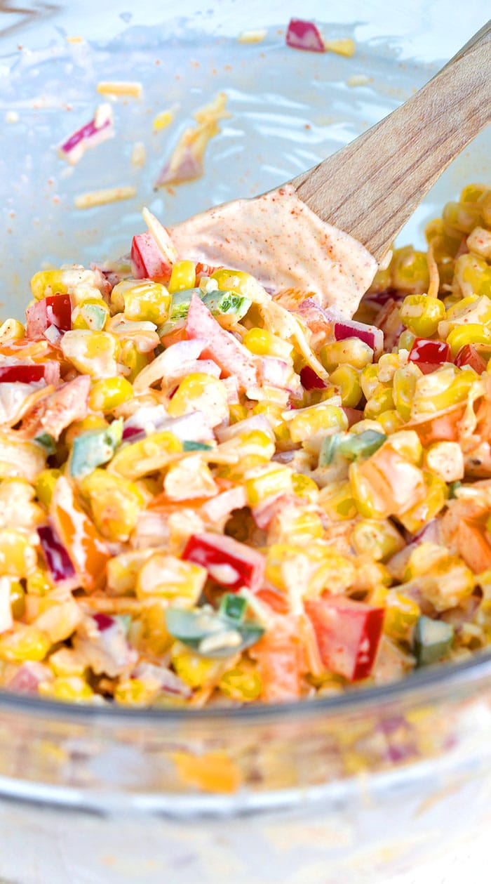 Corn Salad being stirred with a spatula.
