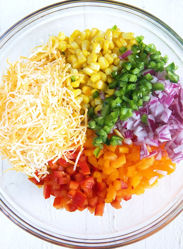 Ingredients for Frito Corn Salad in a glass bowl.