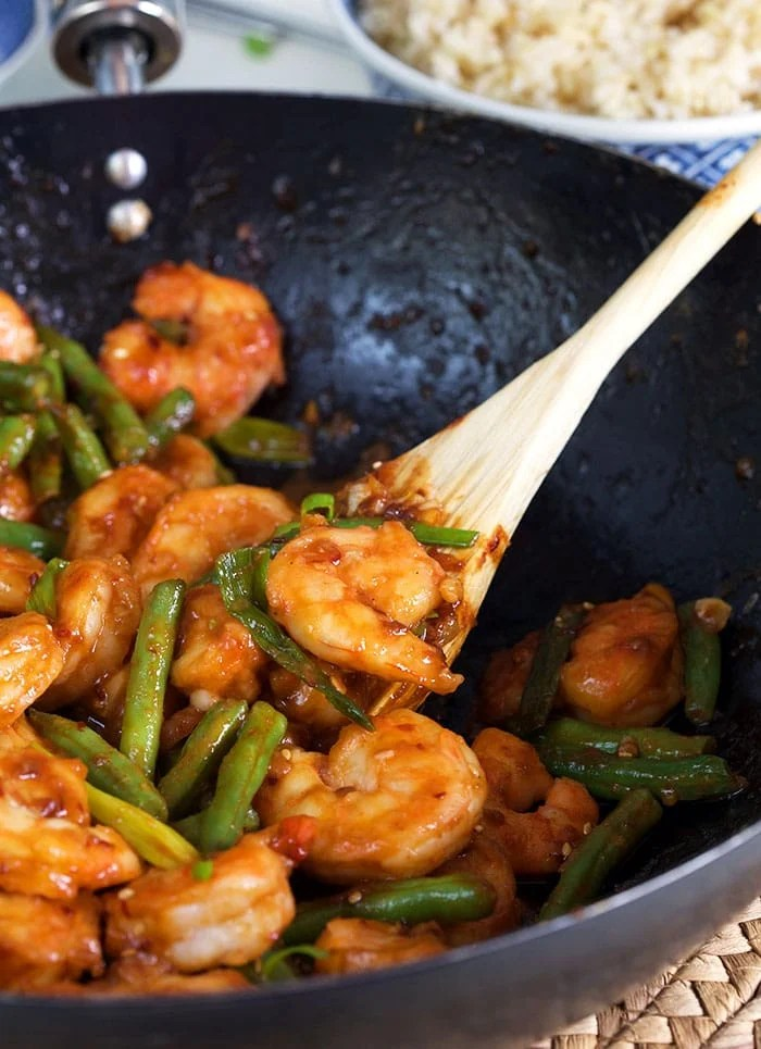 Hunan Shrimp in a stir fry pan with a wooden spoon.