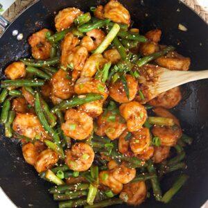Overhead shot of Hunan Shrimp in a black stir fry pan.