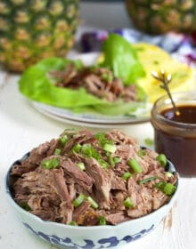 Kalua pork in a blue and white bowl on a white background.