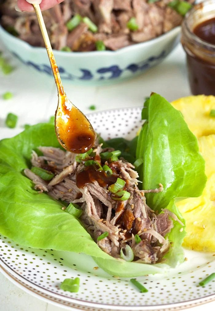 Kalua Pork on a lettuce leaf with a spoon drizzling sauce on top.