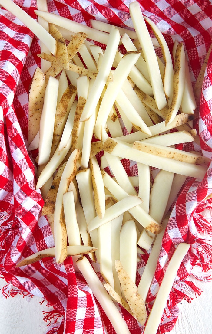 raw French fries on a red and white checkered towels.