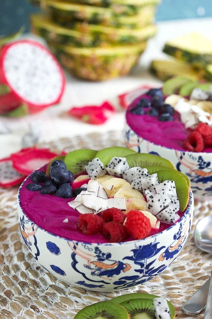 two bowls of Pitaya smoothie bowls with fresh fruit on top