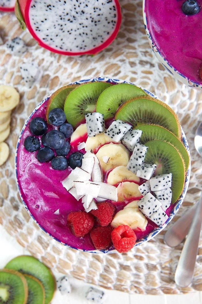 overhead shot of pitaya bowl smoothie bowl with blueberries, kiwi, coconut and raspberries.