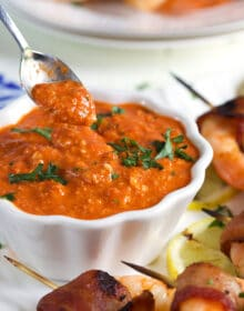 Romesco Sauce in a white bowl with a silver spoon and grilled shrimp on the side.