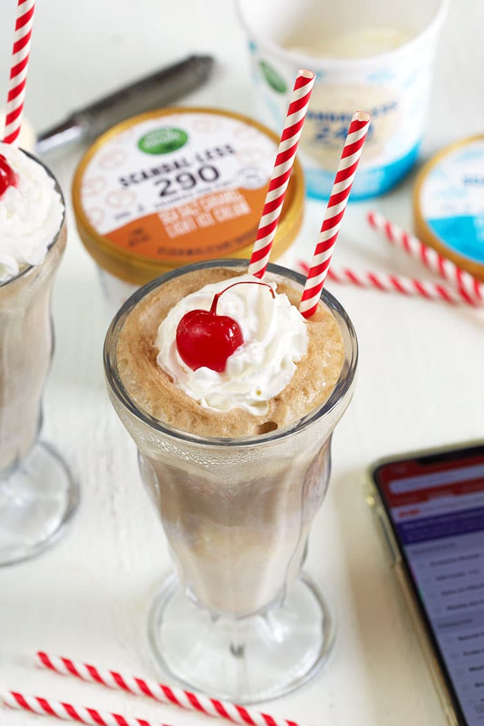 Overhead shot of root beer float with red and white straws.