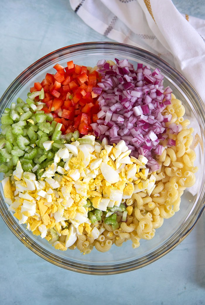 Overhead shot of ingredients for macaroni salad in a glass bowl on a blue background.