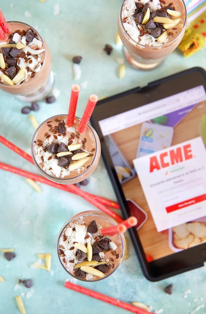Overhead shot of four chocolate banana smoothies on a blue background with an iPad with the ACME shopping app loaded.