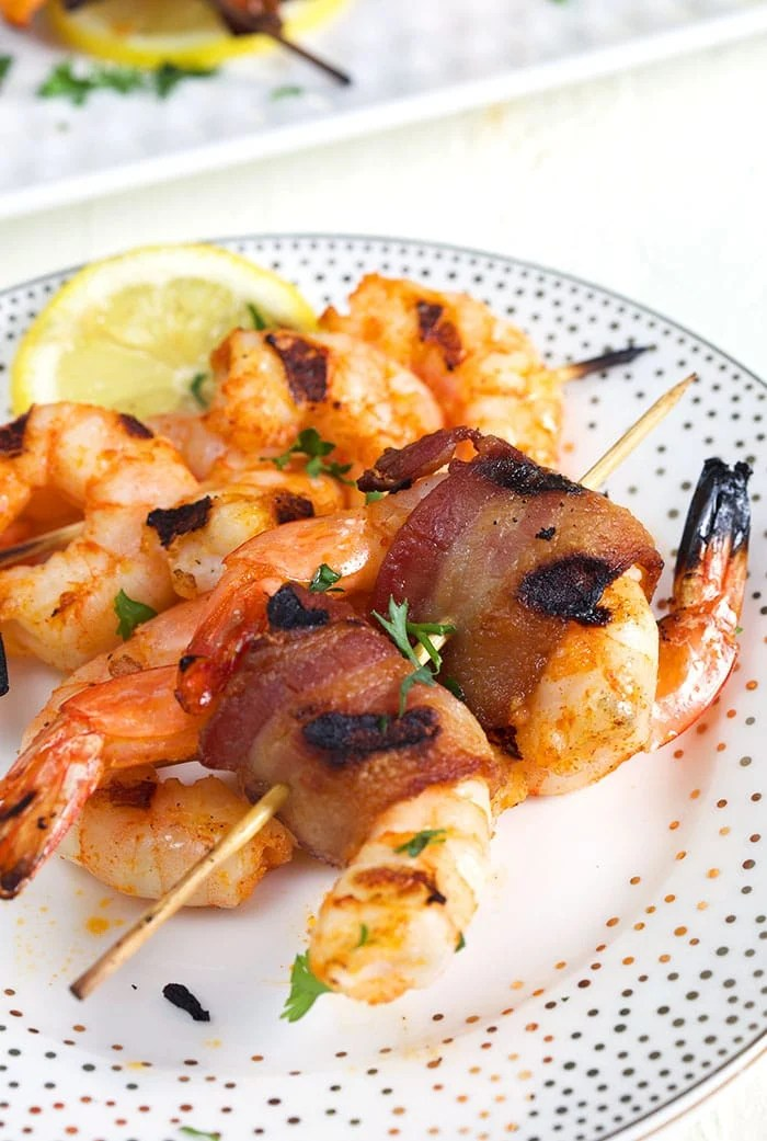 Bacon wrapped shrimp on a bamboo skewer on a white plate with gold polka dots and a lemon slice on the plate.