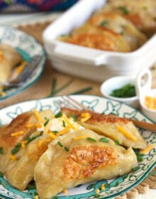 Loaded Baked Potato Pierogi on a blue and white plate.
