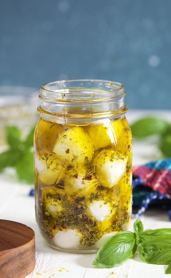 Marinated Mozzarella Balls in a jar with olive oil on a white background with basil leaves.