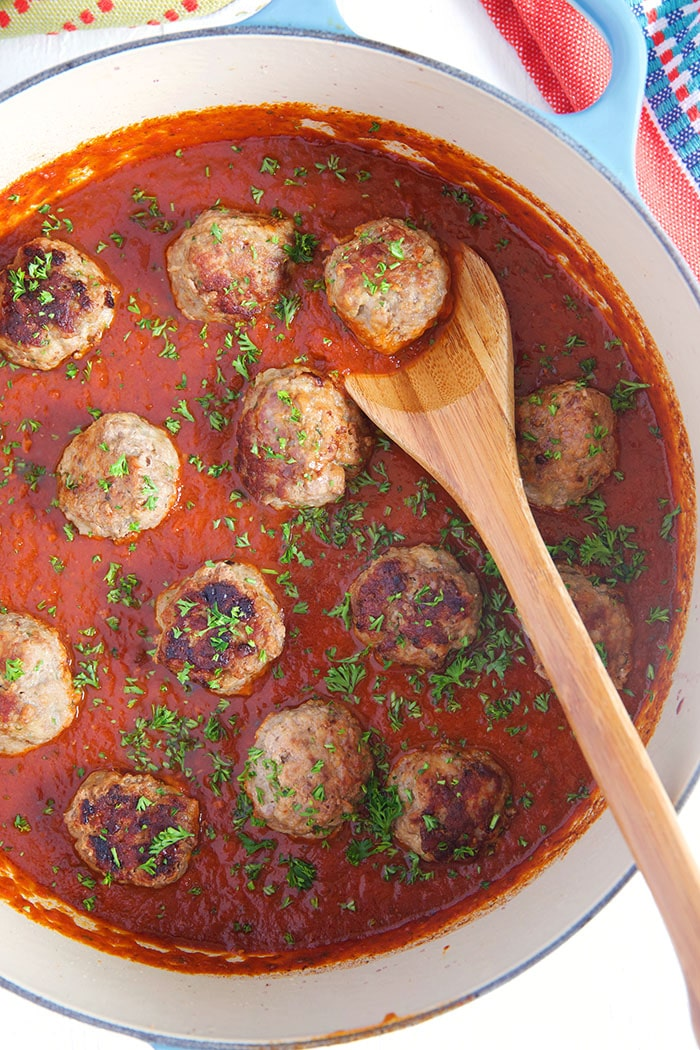Overhead shot of pan fried meatballs in a dutch oven with a wooden spoon and tomato sauce.