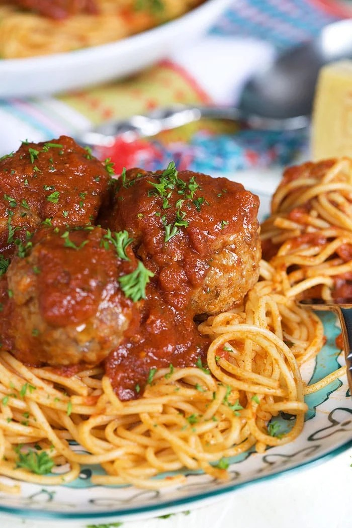 Pan Fried Meatballs on a plate of spaghettini with a fork twirled with pasta.