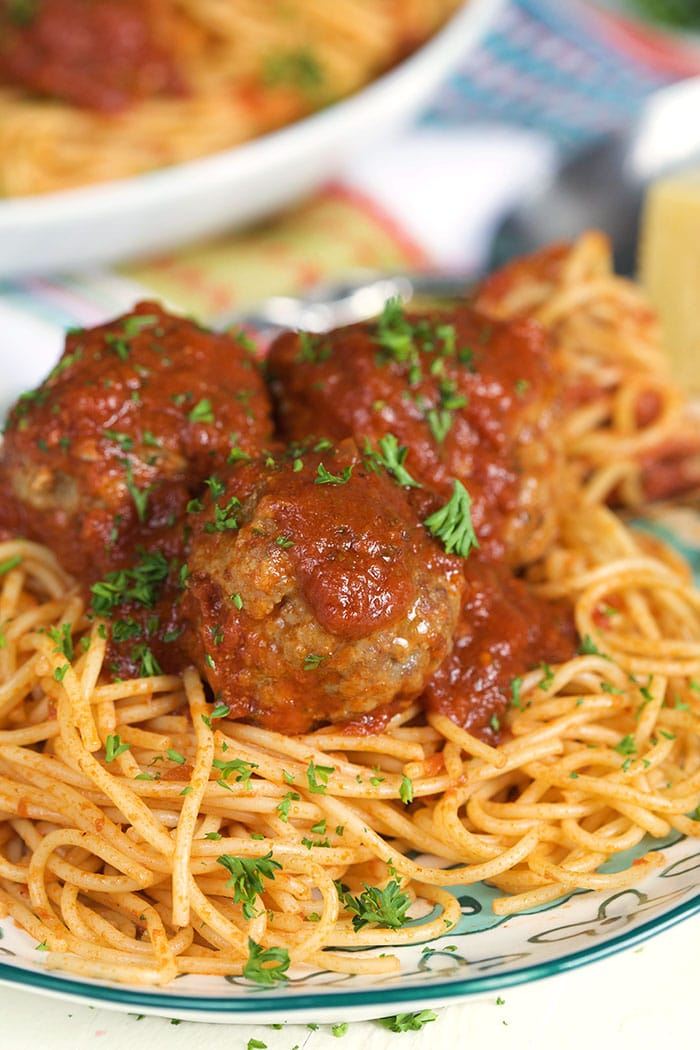 Fried meatballs on a pile of spaghetti on a white plate.