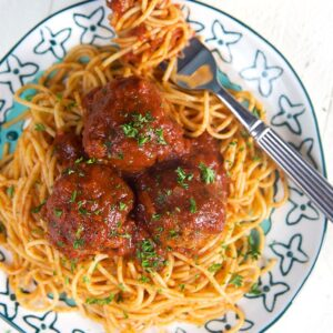Overhead shot of spaghetti and meatballs on a white plate with a turquoise design and a fork with spaghetti swirled around it.