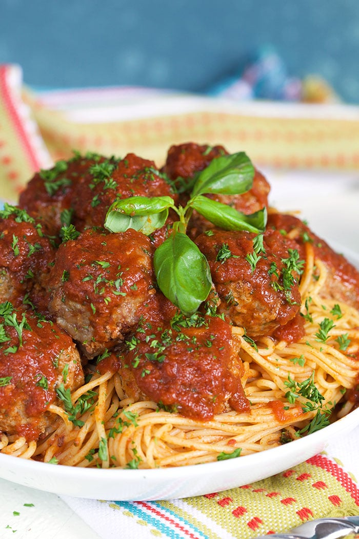 Fried Meatballs on a pile of spaghetti with tomato sauce in a white bowl.