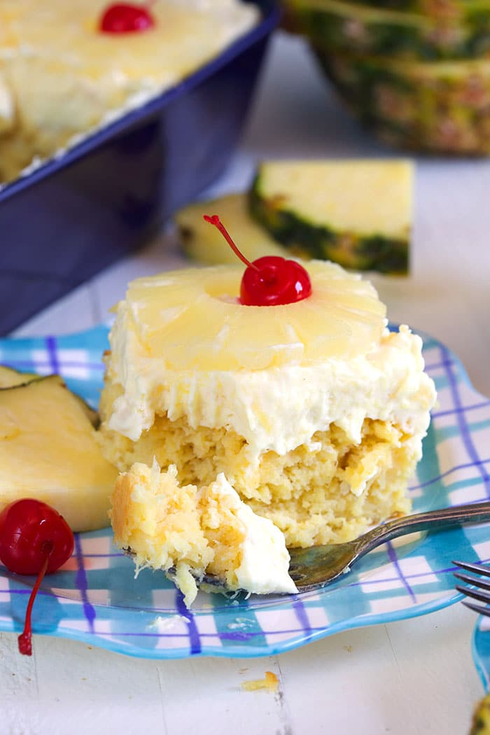 Pineapple sunshine cake with a fork that has a bite on it.