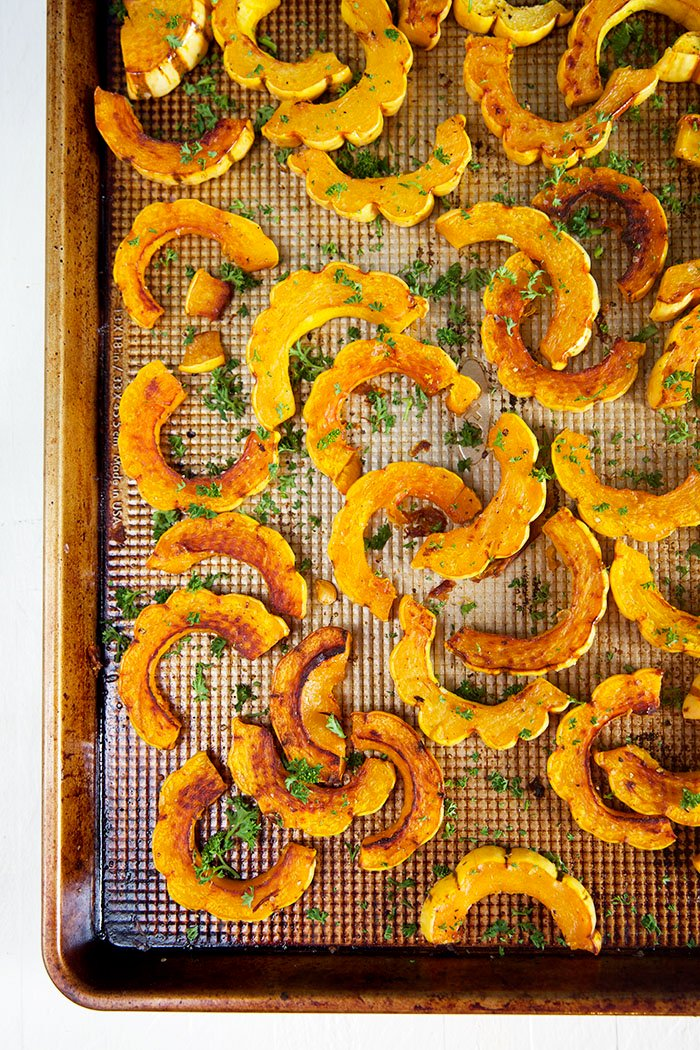Overhead shot of delicata squash on a baking sheet.