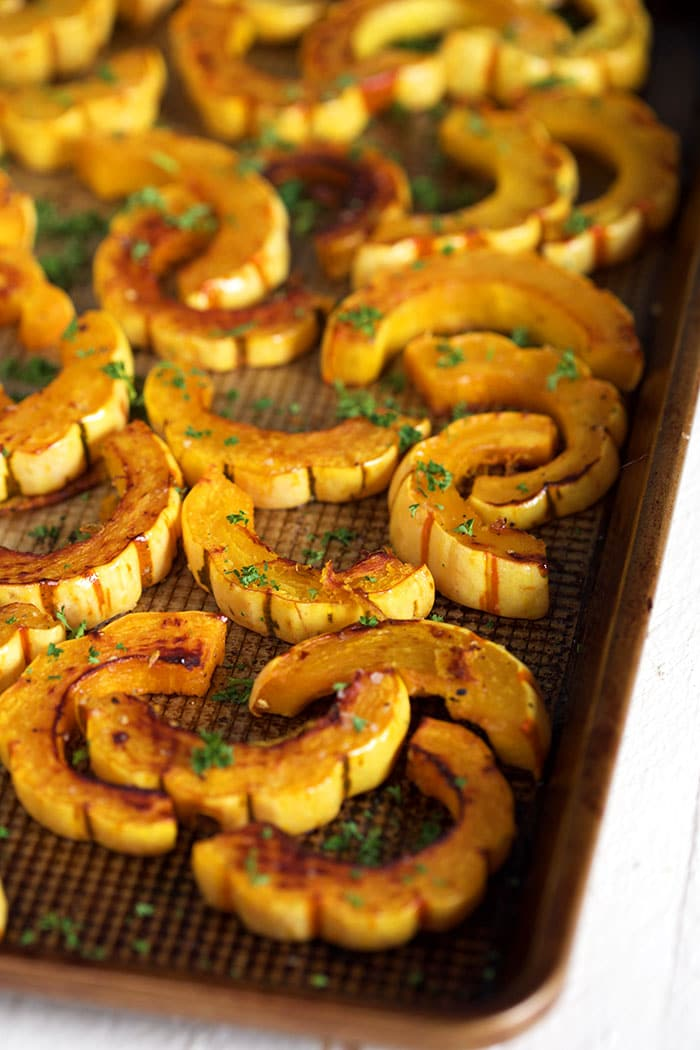 Delicata squash on a baking sheet with parsley sprinkled over it.