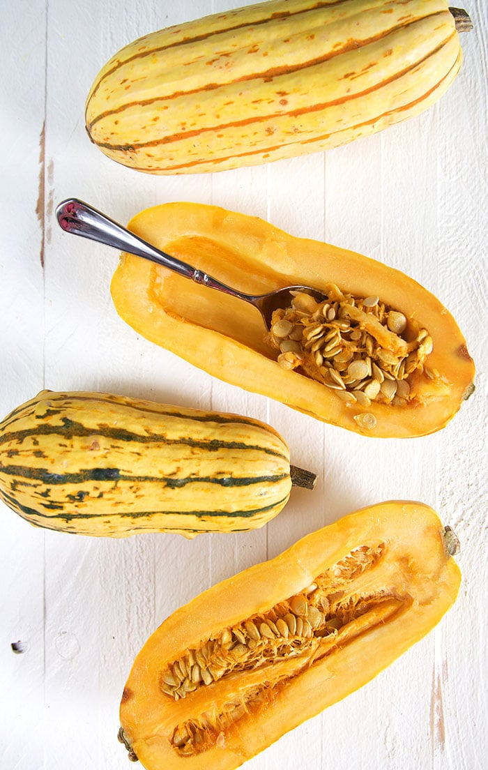Overhead shot of delicata squash cut in half with a spoon scooping out the seeds on a white background.