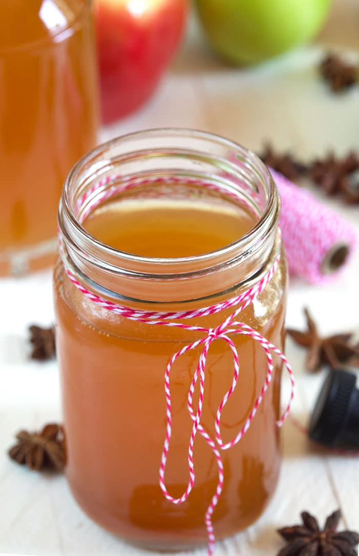 Moonshine in a glass jar with red and white string tied around the top.