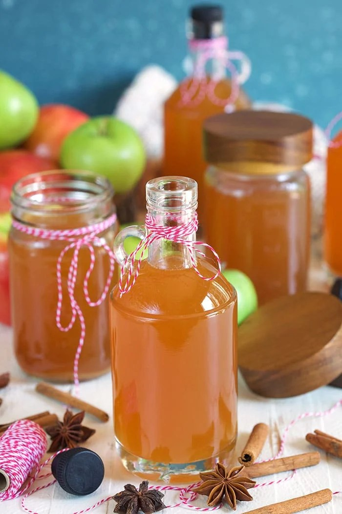 Jars and bottles of apple pie moonshine with a bowl of apples in the background.