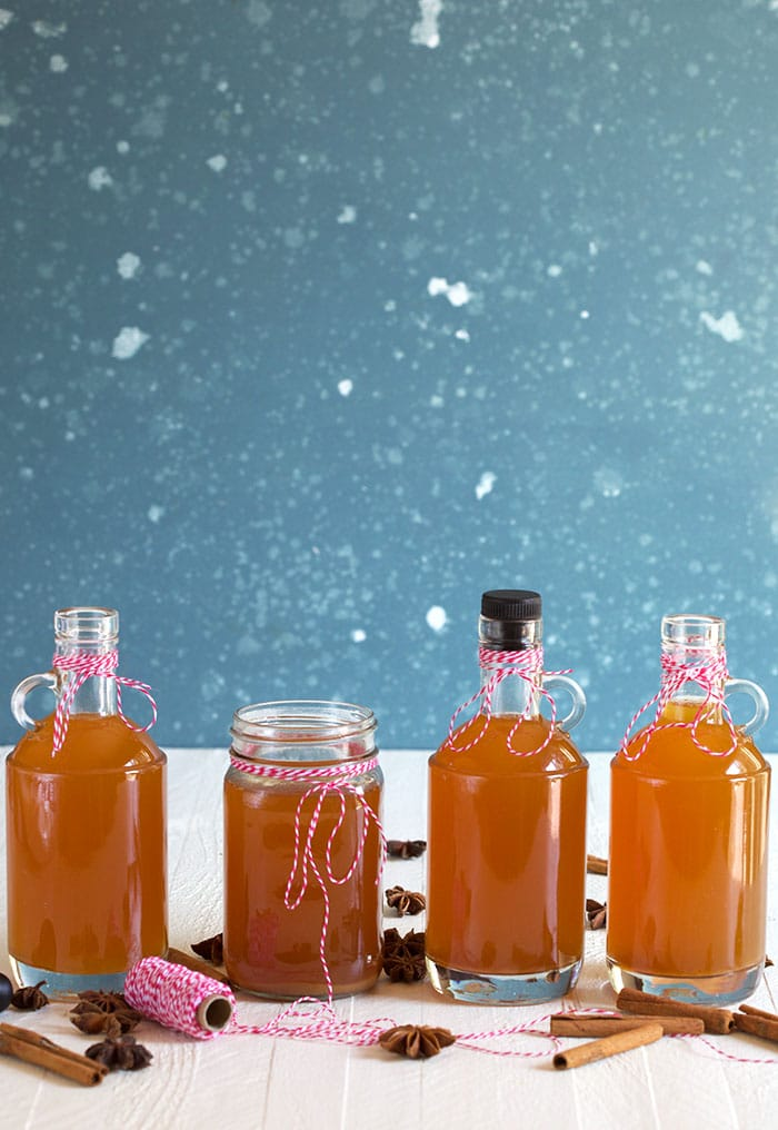 Bottles of apple pie liquor on a blue and white background.