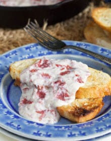Close up of creamed chipped beef on toast on a blue plate.