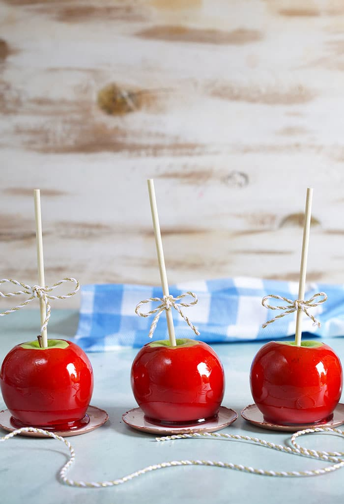 Three candy apples in a row on a blue background.