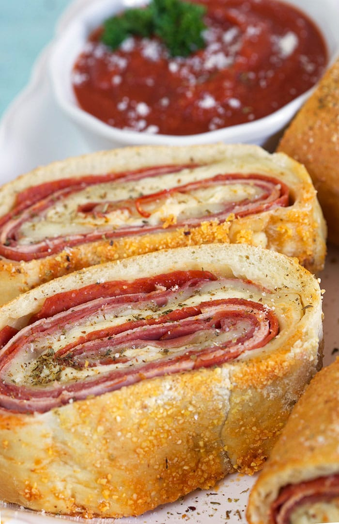 Stromboli sliced next to a white bowl of marinara sauce.