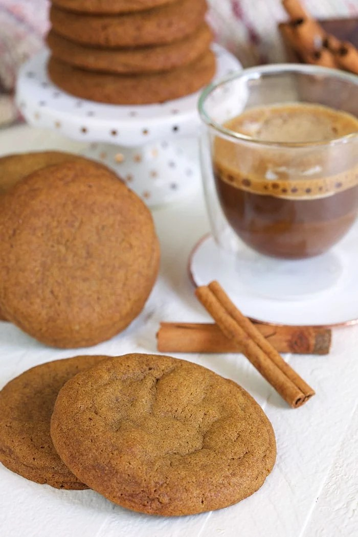 Gingersnap cookies on a white background with a cup of coffee in a glass mug.