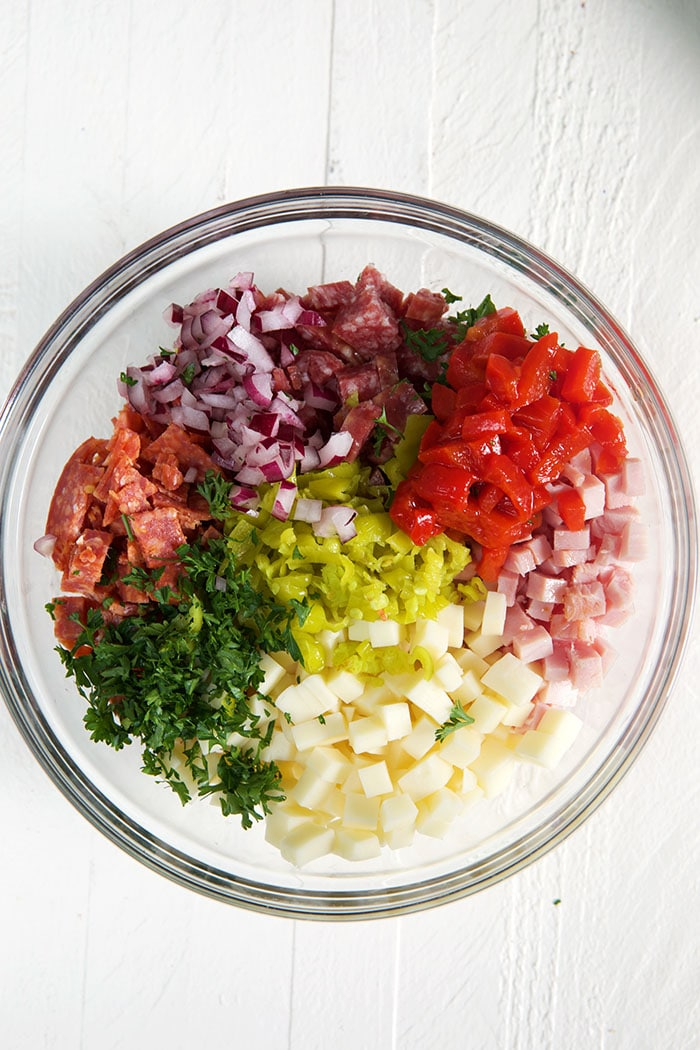 Ingredients for hoagie dip in a glass bowl on a white background.