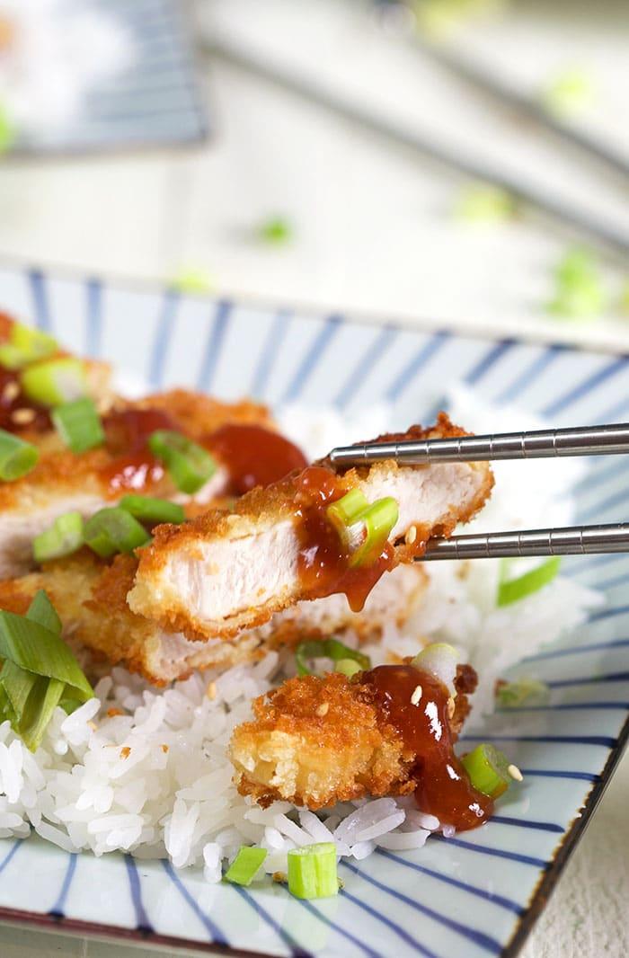 Pork Katsu being served with silver chopsticks.