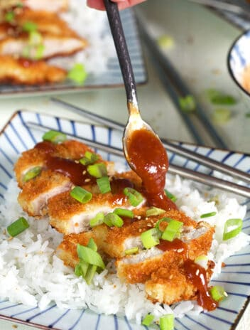 Tonkatsu on a bed of rice with sauce being drizzled with a spoon.