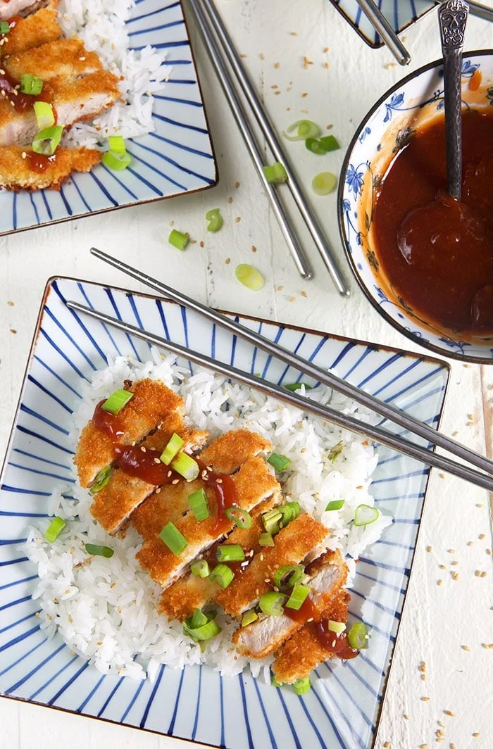 Overhead shot of Pork Katsu on a square blue and white striped plate with white rice.